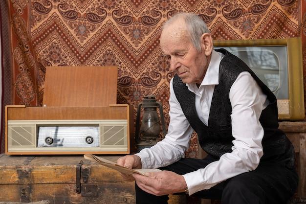 Dziadek w białej koszuli siedzi przy starym radiu i czyta gazetę