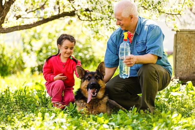 Dziadek z psem wnuczką i psem w ogrodzie
