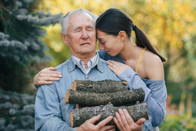 Dziadek z wnuczką na podwórku z drewna opałowego w ręce