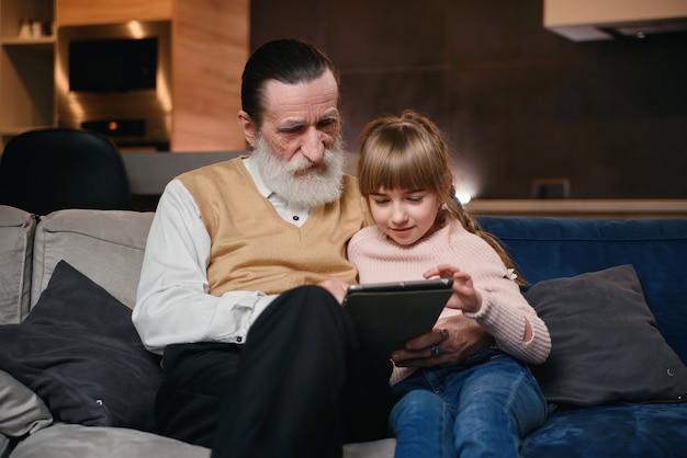 Dziadek z wnuczką za pomocą tabletu w domu