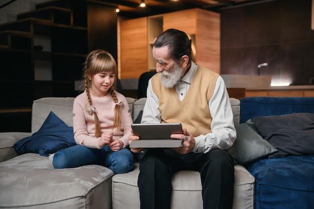 Dziadek z wnuczką za pomocą tabletu w przytulnym domu.
