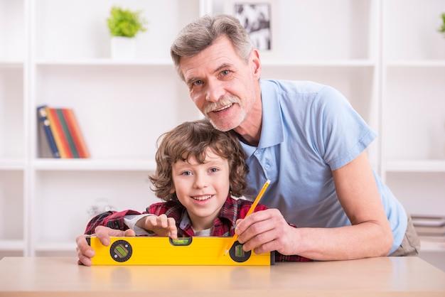 Dziadek z wnukiem mierzy poziom stołu.