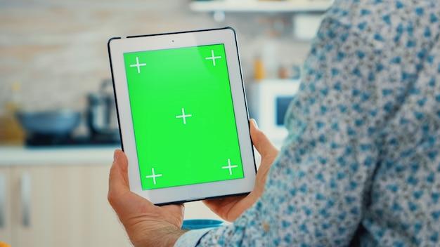 Dziadka przy użyciu komputera typu tablet z zielonym ekranem w kuchni, ciesząc się jego śniadaniem. osoba w podeszłym wieku z wyizolowaną makietą chroma key dla łatwej wymiany