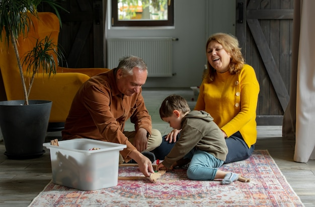 Dziadkowie bawią się w kolejkę z wnukiem w domu.