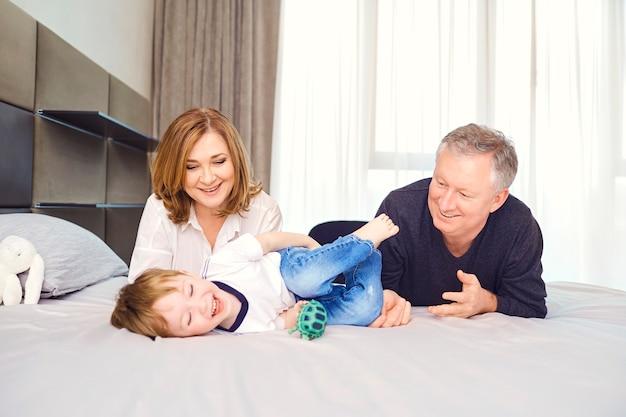 Dziadkowie bawią się z wnukiem dziecka na łóżku w pokoju