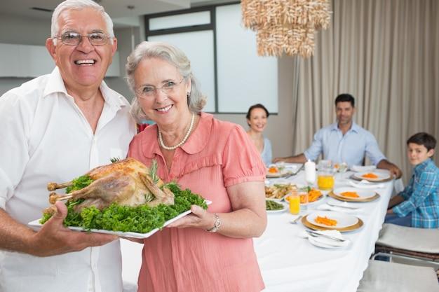 Dziadkowie gospodarstwa kurczaka pieczeń z rodziną przy stole jadalnym