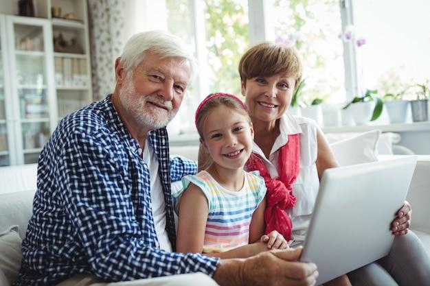 Dziadkowie i wnuczka korzysta z laptopa w salonie