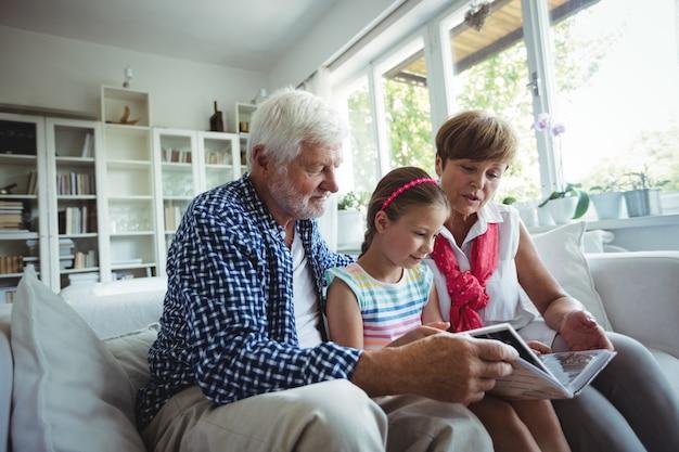 Dziadkowie i wnuczka patrząc na album ze zdjęciami w salonie