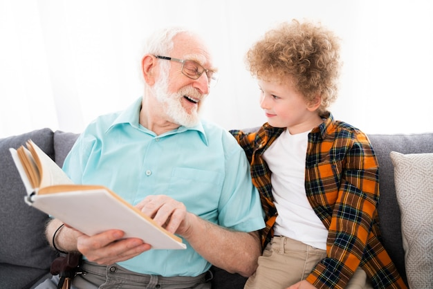Dziadkowie i wnuk bawią się w domu - rodzina w domu, dziadek opiekujący się siostrzeńcem