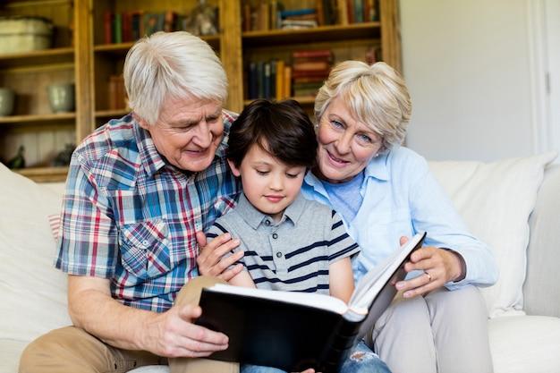 Dziadkowie i wnuk patrząc na album ze zdjęciami w salonie