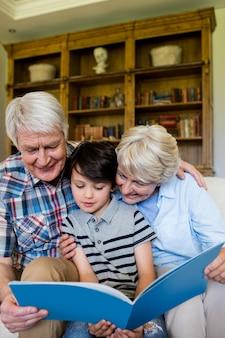 Dziadkowie i wnuk patrząc na książkę w salonie