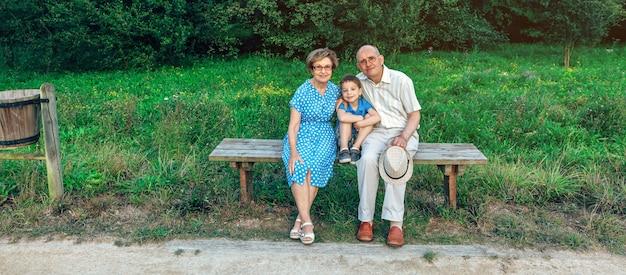 Dziadkowie i wnuk pozują do zdjęcia siedząc na ławce na świeżym powietrzu