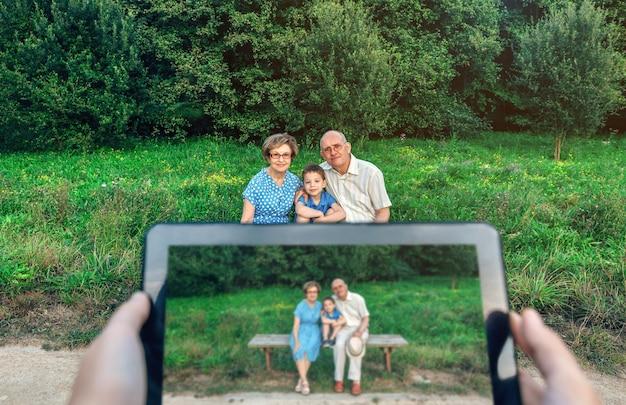 Dziadkowie i wnuk pozują, gdy ktoś robi zdjęcie tabletem. selektywne skupienie się na rodzinie w tle