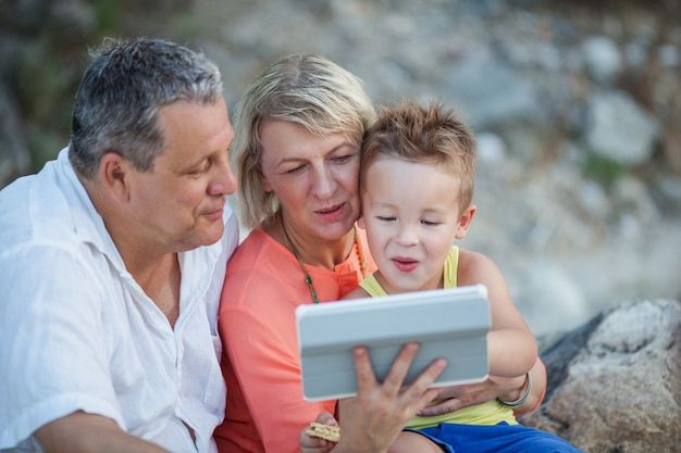 Dziadkowie i wnuk z tablet pc na zewnątrz