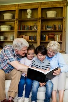Dziadkowie i wnuki oglądają album ze zdjęciami w salonie