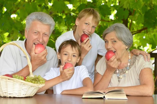 Dziadkowie i wnukowie z jabłkami latem przy stole
