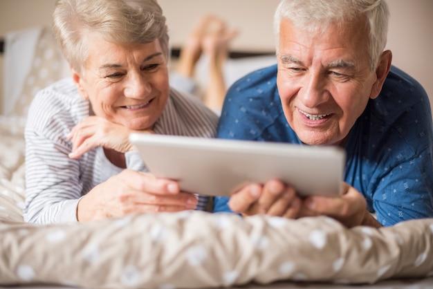 Dziadkowie odpoczywają podczas korzystania z cyfrowego tabletu