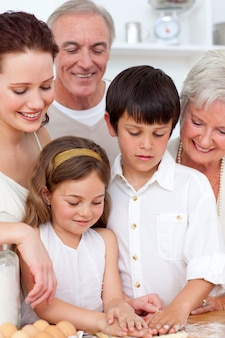 Dziadkowie patrząc na dzieci do pieczenia w kuchni