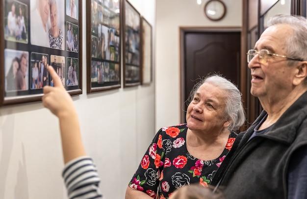 Dziadkowie pokazują rodzinne fotografie wnuczek na ścianie w domu.