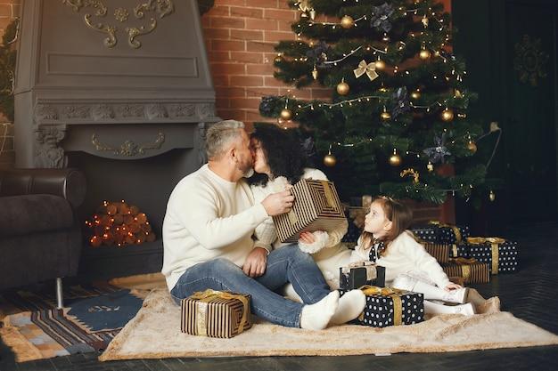 Dziadkowie siedzą z wnuczką. świętowanie bożego narodzenia w przytulnym domu.