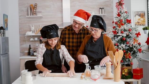 Dziadkowie uczą wnuczkę jak przygotować domowe ciasto na pierniki