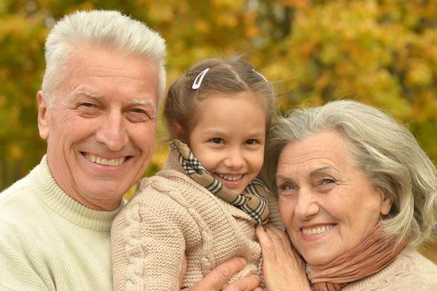 Dziadkowie uśmiechający się z wnuczką odpoczywającą w jesiennym lesie
