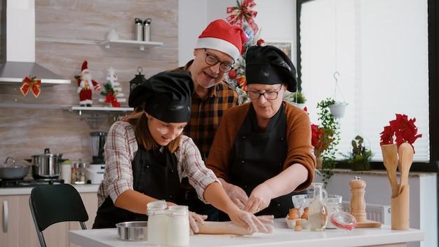 Dziadkowie, wnuk z kawą, robi tradycyjne świąteczne domowe ciasteczka