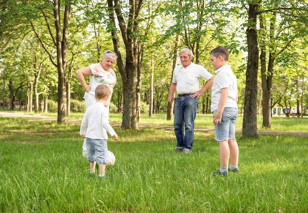 Dziadkowie z małymi uroczymi wnukami grającymi w piłkę nożną