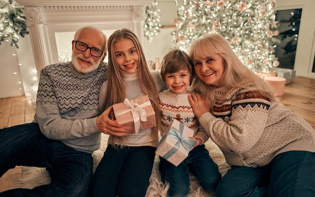 Dziadkowie z prezentami siedzą na podłodze z dziećmi