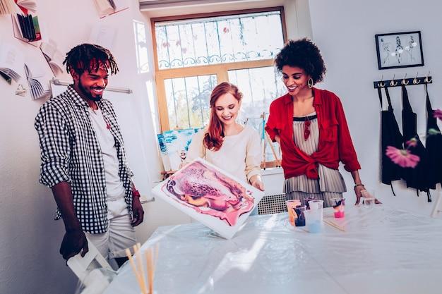 Dział sztuki. trzech wesołych pracowników działu artystycznego zadowolonych z efektu pracy