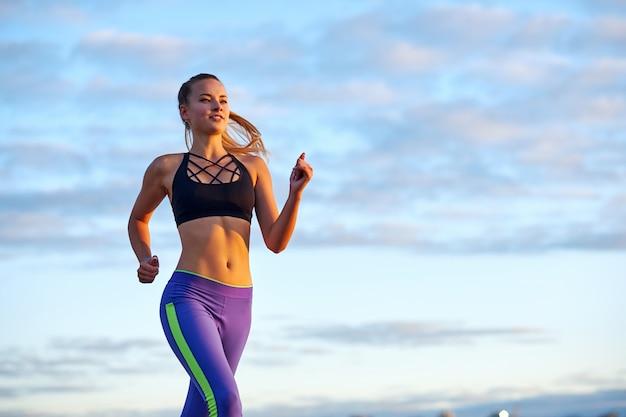 Działa kobieta o wschodzie słońca. ranek jogging na nieba tle