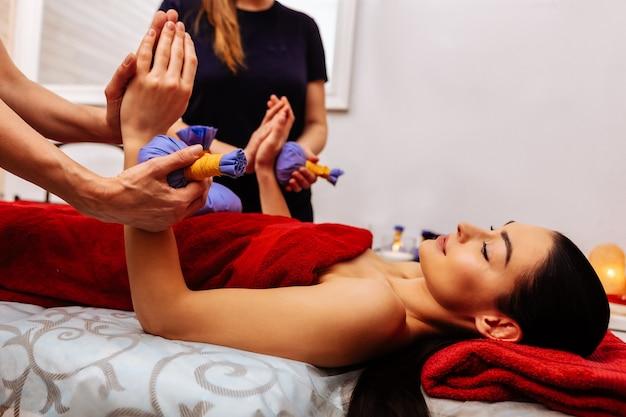 Działa synchronicznie. przyjemna długowłosa kobieta podnosząca ręce podczas zabiegu z niebieskimi workami wypełnionymi ziołami
