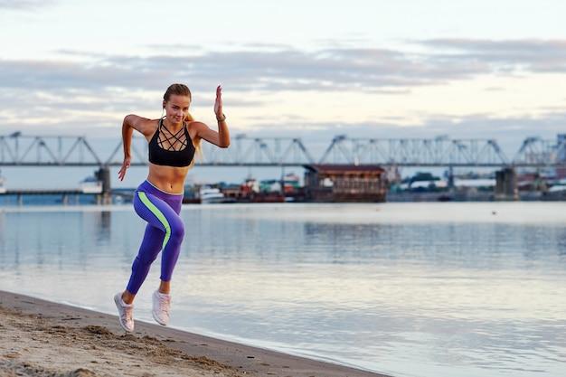 Działająca kobieta w piasku przy wschodem słońca. rano jogging na plaży lub wybrzeżu rzeki na tle miasta miejski