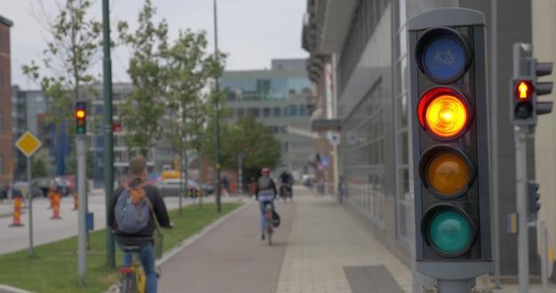 Działająca sygnalizacja świetlna dla rowerów na pierwszym planie, ludzie jeżdżący na rowerach po ulicy w tle