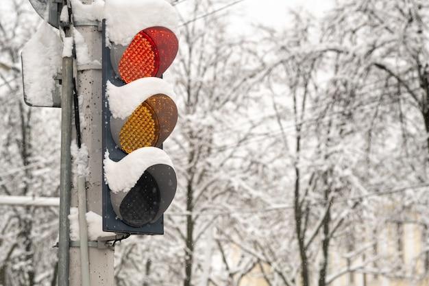 Działające światła drogowe na ulicy miejskiej w zimie. czerwone światło jest włączone.