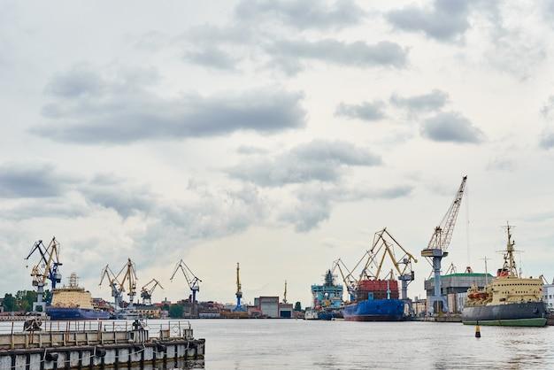 Działający most dźwigowy w stoczni i statki towarowe w porcie