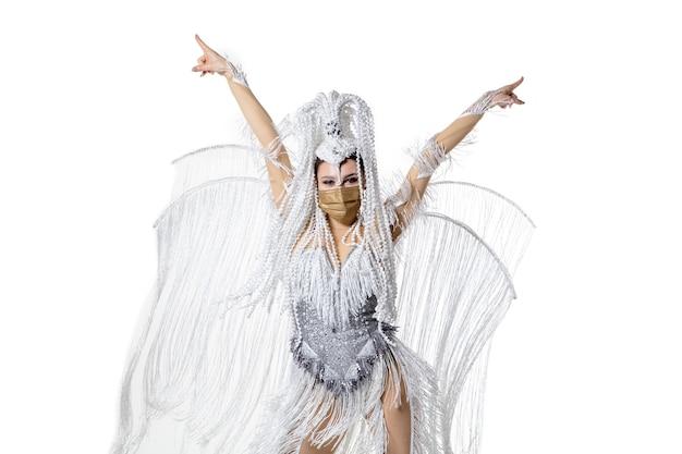 Działający. piękna młoda kobieta w karnawałowym stroju maskaradowym z białymi piórami taniec na białym tle. koncepcja obchodów świąt, czasu świątecznego, tańca, imprezy, szczęścia. copyspace