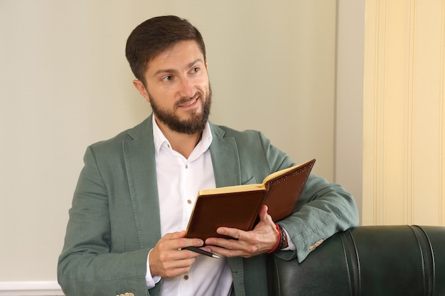 Działający w biurze biznesmen, który odniósł sukces, studiuje dziennik
