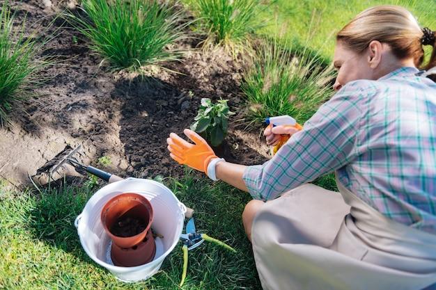 Działalność ogrodnicza. opiekująca się piękną rodzinną kobietą wykonującą prace ogrodnicze w jej wolny weekend