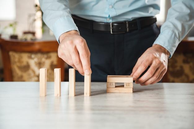 Działalności człowieka grając z drewnianymi kostkami na biurku