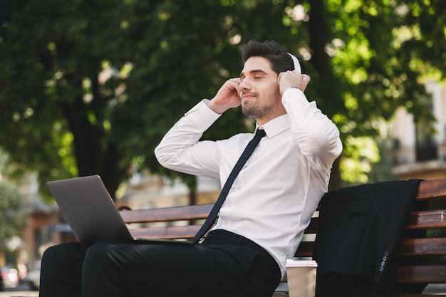 Działalności człowieka na zewnątrz w parku przy użyciu komputera przenośnego słuchania muzyki.