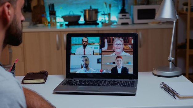 Działalności człowieka o spotkanie firmowe przy użyciu laptopa pracującego zdalnie późno w nocy. przy użyciu nowoczesnej technologii sieci bezprzewodowej rozmawiając podczas wideokonferencji o północy robiąc nadgodziny