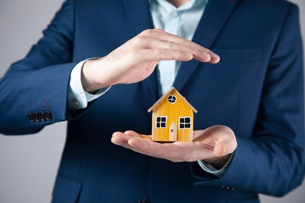 Działalności człowieka posiadającego drewniany model domu