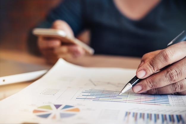 Działalności człowieka pracującego z dokumentem finansowym w biurze otwartej przestrzeni. raport ze spotkania w toku.