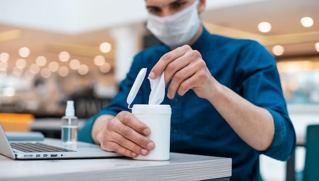 Działalności człowieka przy użyciu chusteczek antyseptycznych siedzi przy stole