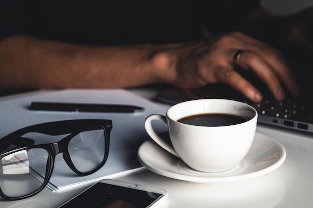 Działalności człowieka przy użyciu komputera przenośnego i ręcznie wpisując na klawiaturze laptopa w okularach długopis notebooka i filiżankę gorącej kawy