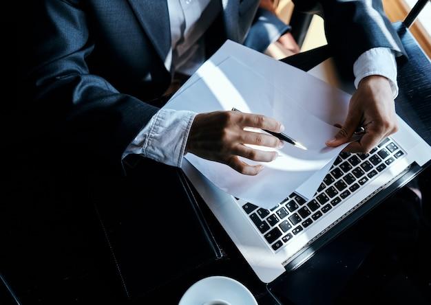 Działalności człowieka siedzącego w kawiarni przed laptopem dokumenty filiżanka kawy wykonawczy technologia stylu życia widok z góry. wysokiej jakości zdjęcie