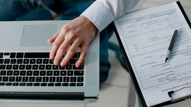 Działalności człowieka używa laptopa do pracy z dokumentami