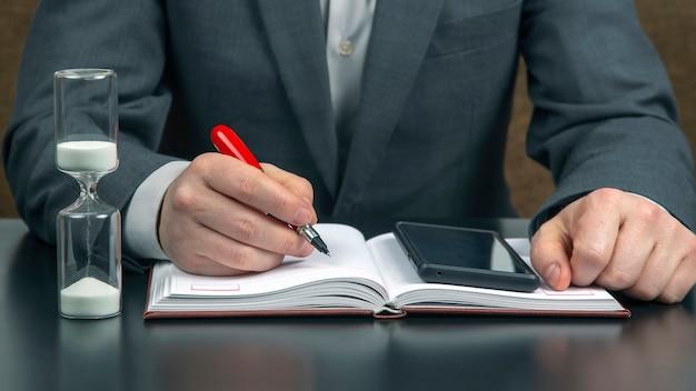 Działalności człowieka w biurze pracuje na tle klepsydry. biznes i udany cel