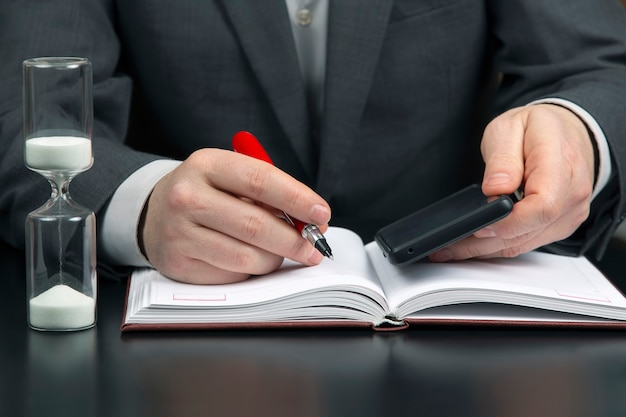Działalności człowieka w biurze pracuje z telefonem komórkowym na przestrzeni klepsydry. biznes i udany cel